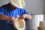 This guy is cutting the edges of the hats, since 30 years...